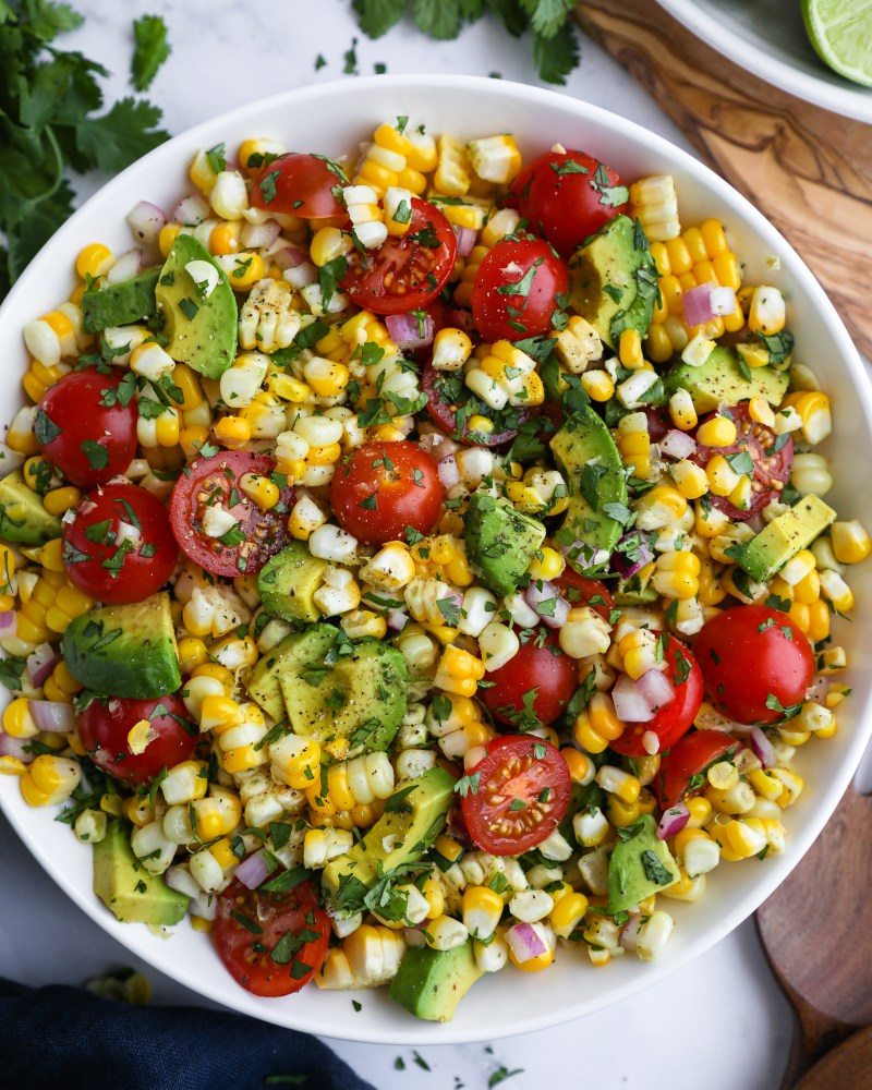 Fresh summer corn salad in a white bowl topped with cilantro surrounded by a blue linen napkins, a bundle of cilantro and lime wedges