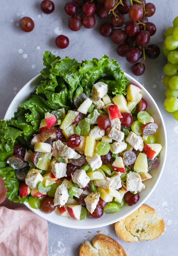 Chicken salad made with red grapes, green grapes, apples, pineapple, celery and mayo served in a large white bowl with lettuce on the side