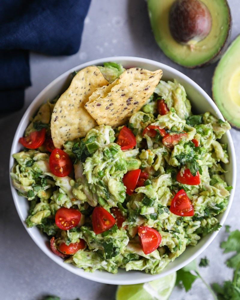 Chicken salad made with mashed avocados, lime juice and cilantro served in a small white bowl with tortilla chips