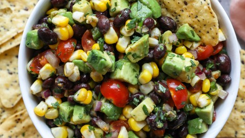 Black bean, avocado and corn salsa with a tortilla chip sticking out of the bowl
