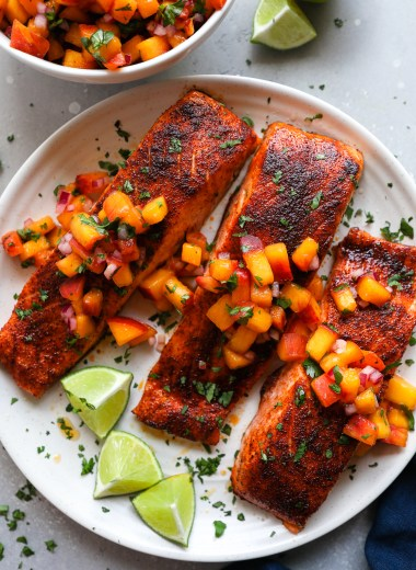 3 roasted chipotle salmon fillets sitting on a white plate with spoonfuls of fresh peach salsa on top