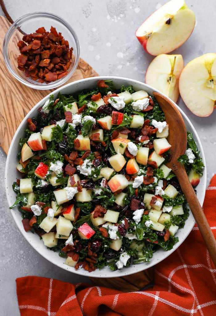 Chopped kale salad served in a large bowl surrounded by a jar of cooked bacon bits, diced apples and wooden salad tongs