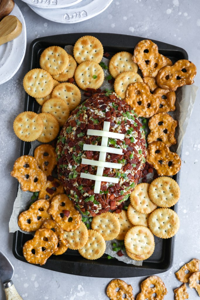 A football shaped cheese ball surrounded by Ritz cracker and pretzels on a serving tray