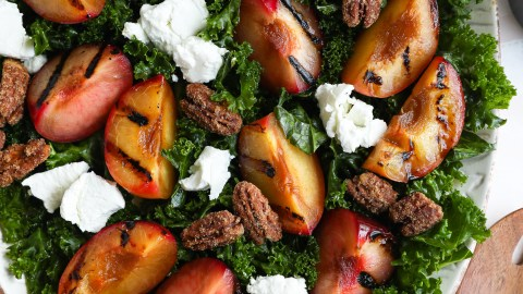 Grilled plumcot kale salad served on a large oval tray topped with candied pecans