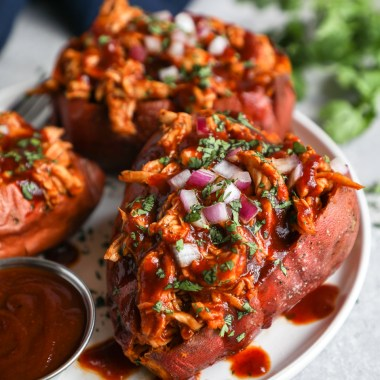 A roasted sweet potato stuffed with shredded bbq chicken and topped with red onion, cilantro and more bbq sauce