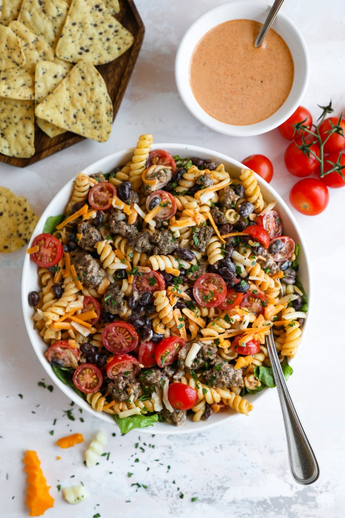 A large white serving bowl filled with rotini pasta, ground beef, black beans, tomatoes, cheese and lettuce