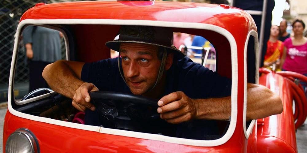 Image d'un spectacle de Chalon dans la rue 2013 représentant un comédien dans un mini camion de pompier dans les rues piétonnes de Chalon-sur-Saône.