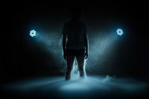 Un danseur dans la pénombre et la fumée, éclairé seulement par deux projecteurs.