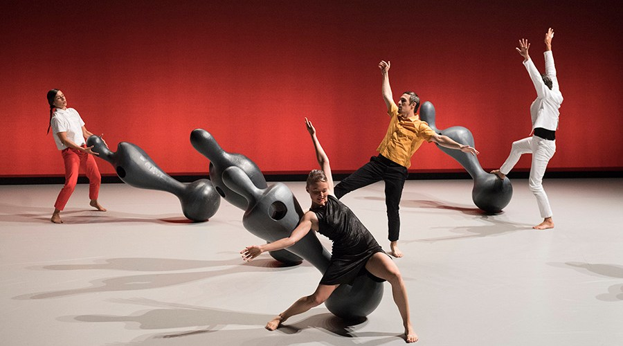 Des danseurs sont en mouvement autour de sculptures biomorphiques à échelle humaine.