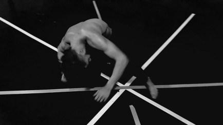 Le danseur est en mouvement. Au sol : des lignes blanches graphiques formant une étoile.