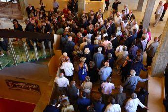 Des centaines de personnes se pressent dans le grand espace pour écouter les discours d'inauguration