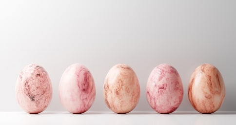 5 pink and white marble easter eggs on white background