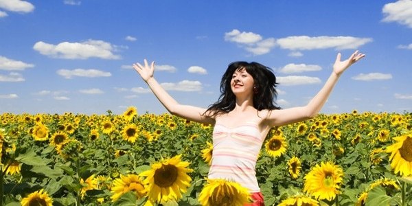woman triumphant in field of sunflowers