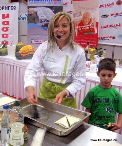 Chef Dina Nikolaou cooking for an audience at the Thessaloniki Fair