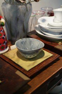 京都在住、藤平寧(やすし)さんの飯碗、7,350円。夏の抹茶碗に見立てで使う方もいるそうです。後ろに写っているガラスの花器はパート・ド・ヴェールの作家、飯塚亜裕子さんの作品、63,000円。ドームやガレの技法でつくります。