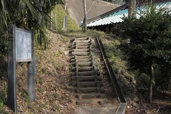 衣笠城址は大善寺の裏山です。写真右上に見えているのは大善寺本堂の軒先。中央の階段を登って行きます。