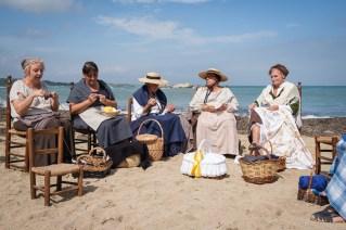 Mujeres tejiendo en la playa.