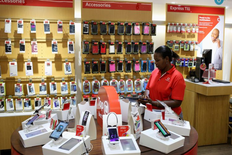 A worker cleans cell phone accessories at a Vodacom shop in Johannesburg February 4, 2015. South African telecoms operator Vodacom on Wednesday posted third-quarter revenue of 19.99 billion rand ($1.76 billion), down 1.1 percent from a year earlier, partly due to a drop in the charge customers pay to call other networks. The unit of Britain's Vodafone Plc did, however, add 9 percent more customers to 61.1 million users, in the three months to end December 2014, the company said.(SOUTH AFRICA - Tags: BUSINESS TELECOMS) - RTR4O5QZ