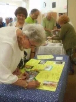 Bep signs Muriel's birthday card.