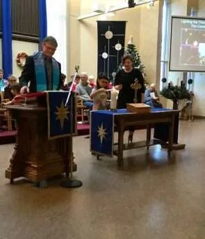 Rev. Bruce with Natika and Eden lighting the Christ Candle
