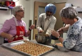 Donna, Manno (with both hair net and beard net) and Becky getting ready to slip the cookies in the oven.