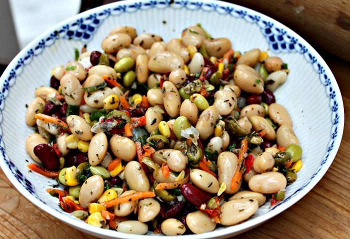 Salat med bønner, gulerod, majs, rød peberfrugt, oliven og krydderurter