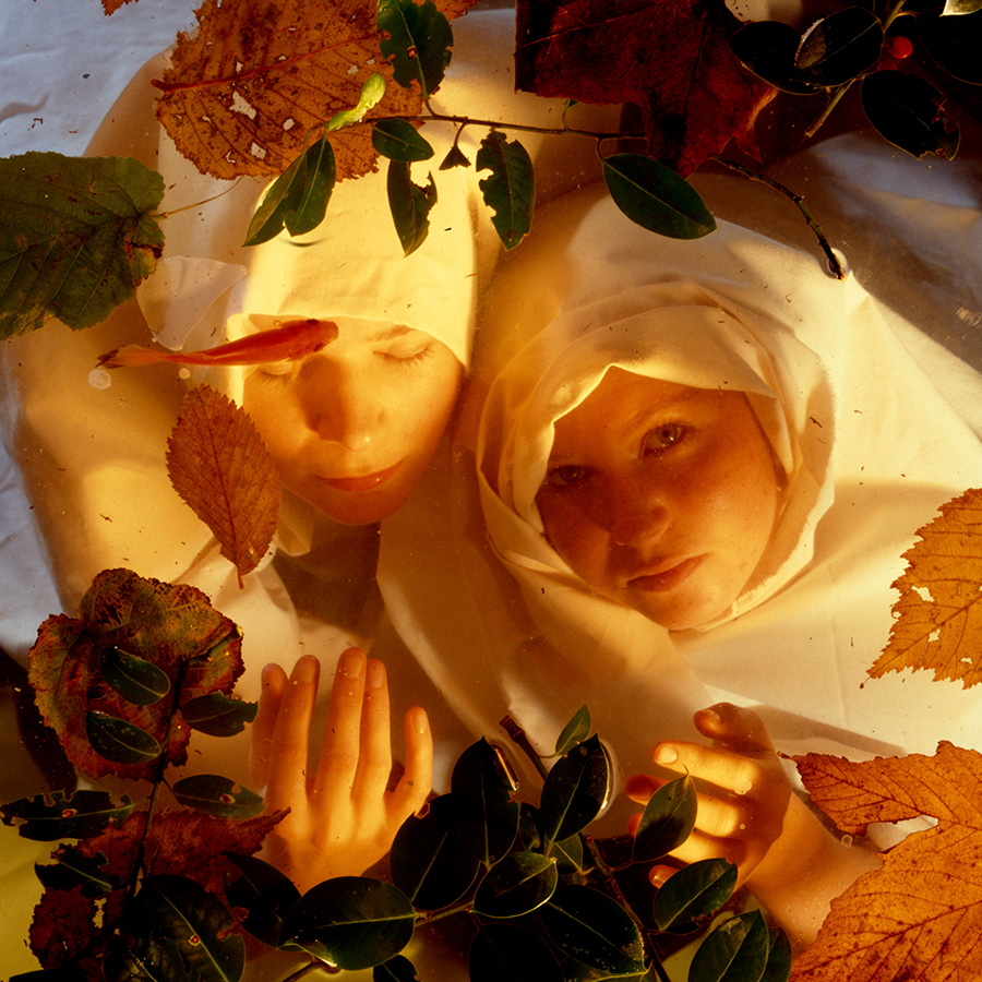 Two white woman, early 20s, cloaked in white, under water with leaves on top. Shot from above