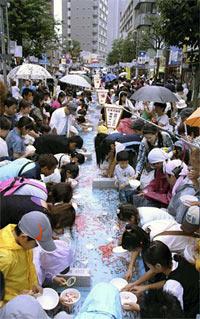 長さ63メートルの巨大水槽で金魚すくいを楽しむ来場者たち/ YOMIURI ONLINE(読売新聞)より