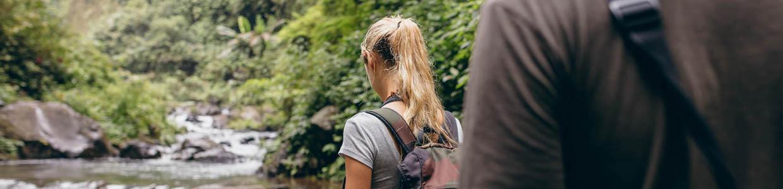 Eine Frau und ein Mann wandern durch eine wilde Flusslandschaft
