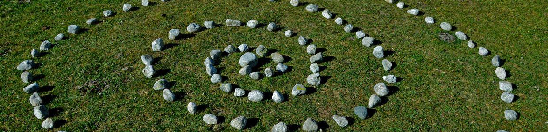 Eine Spirale aus hellen Steinen auf einer Wiese