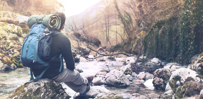 Ein junger Mann mit Trekkinrucksack sitzt in einem Bachlauf auf einem Stein