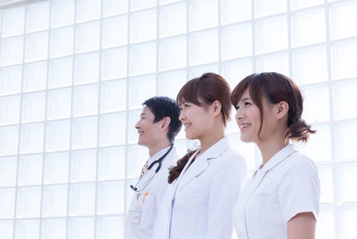 病院内で微笑む女性看護師と女性医師・男性医師