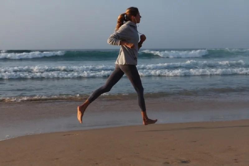 海辺の砂浜を走る女性