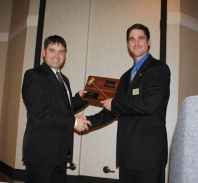 Charly Cummings, the Bid Call Champion for 2009 is presented his plaque by Byron Bina.