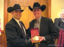Charly Cummings presents Blaine Lotz with the buckle for the livestock contest