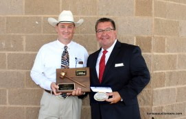 Lance Fullerton, 2014 Champion, presents Lenny Mullin with the 2015 Kansas Auctioneer Championship belt buckle and plaque.