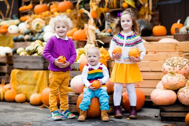 Kansas City fall festivals - three young kids holding pumpkins