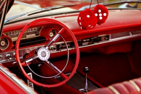 Downtown Belton Cruise Night - steering wheel and dash interior of classic America car colored red with fuzzy dice