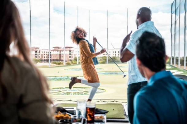 Weekly specials at Top Golf - woman laughing and posing with a golf club