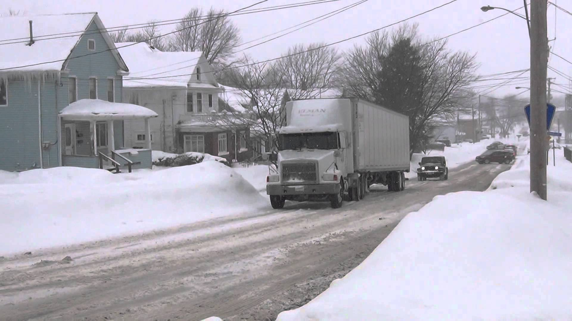 Semi Truck Spins its  Tires Up Snow Covered Hill