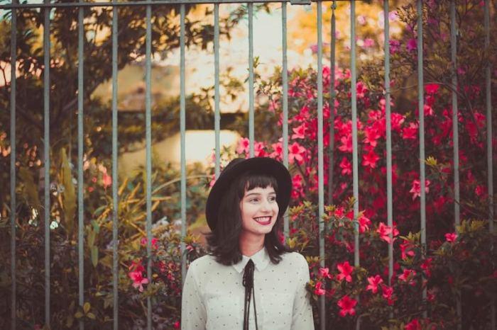 フェンスの前で微笑んでいる女性の画像
