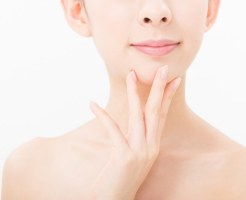 自分の顎に指をあてがう女性の画像
