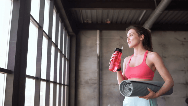 videoblocks-fitness-woman-drinking-water-from-bottle-muscular-young-female-at-gym-taking-a-break-from-workout-20s-4k_rtodjivk_thumbnail-full01