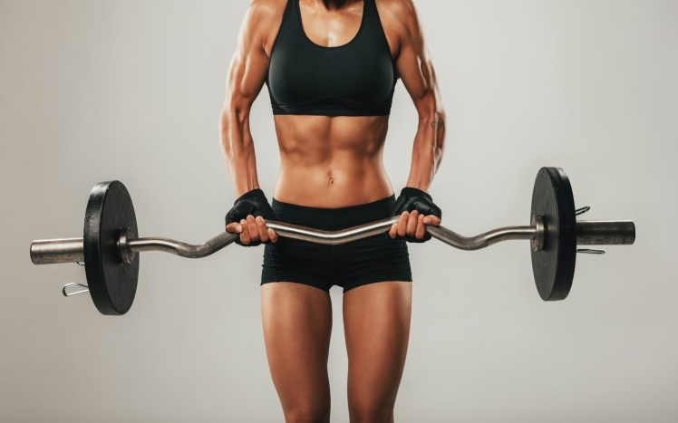 Muscles buldging on arms of woman using barbell