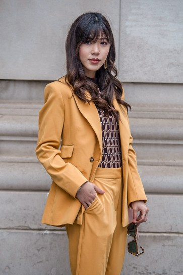 Street Style during day two of London Fashion Week AW 2019. Image shows fashion blogger Kim Bouy Tang wearing a mustard coloursuit.