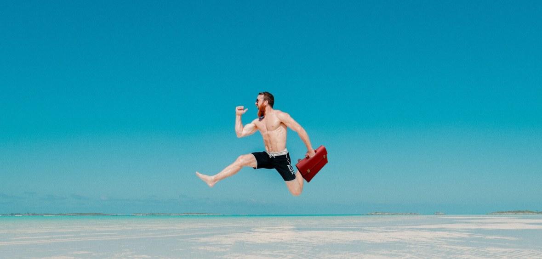 Mann in Badehose mit Aktenkoffer springt am Strand fröhlich in die Luft.