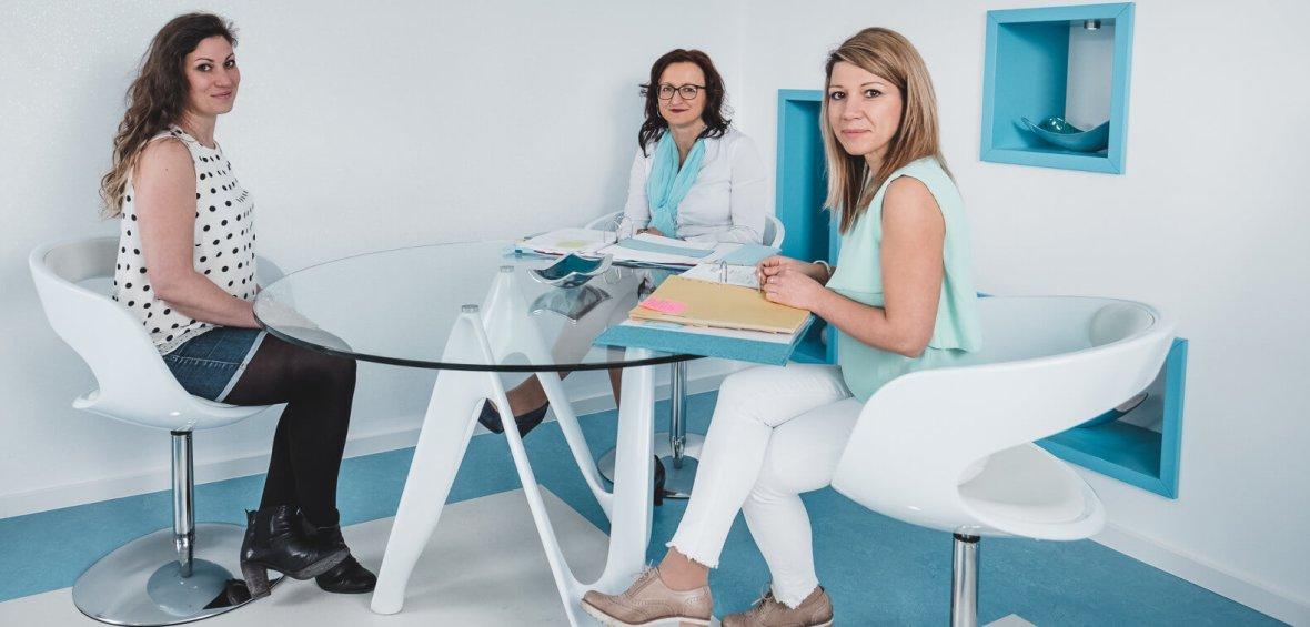 Drei Business Frauen sitzen an einem runden Glastisch.