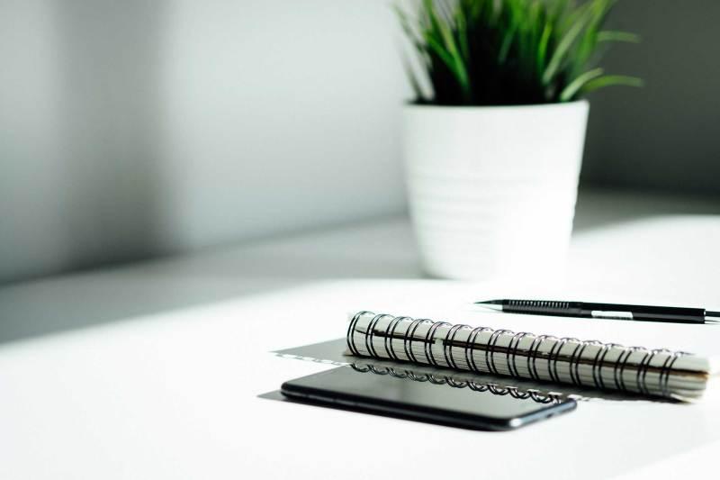 Ein schwarzer Stift liegt auf einem Block neben einem Handy und einer Pflanze auf einem Schreibtisch