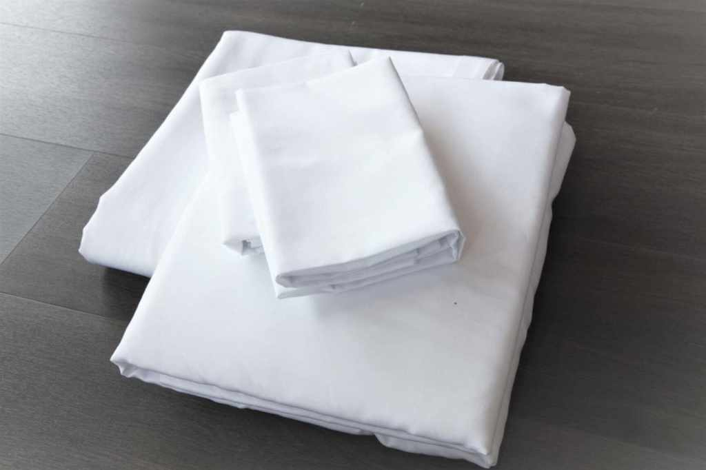 Folded white bed sheets 100% cotton