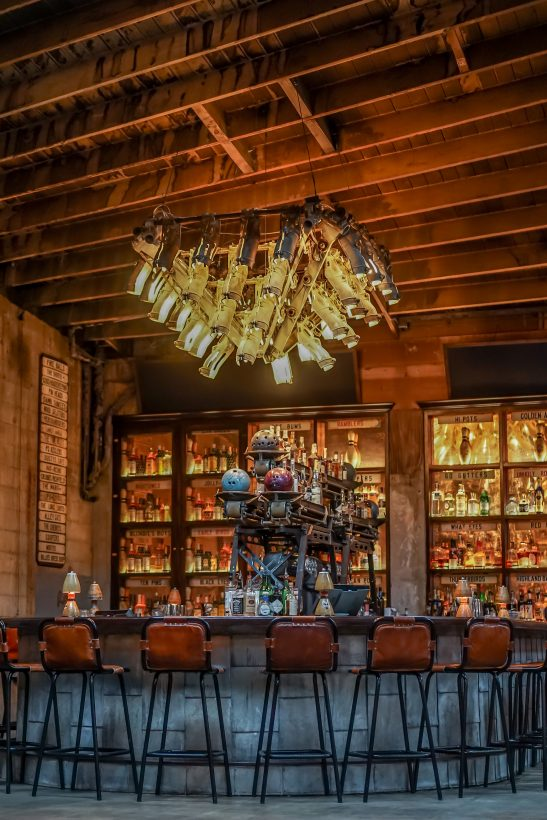 A beautiful old bar with bowling pins used for lights.